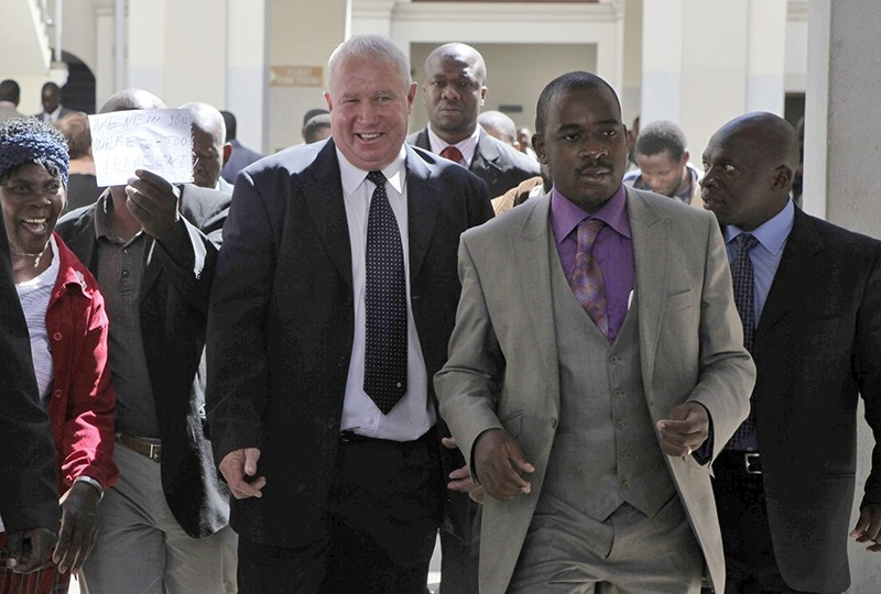 In this May, 10, 2010, file photo, Roy Bennett, center left, leaves the High Court in Harare, Zimbabwe, after he was acquitted of terrorism charges. (AP Photo)