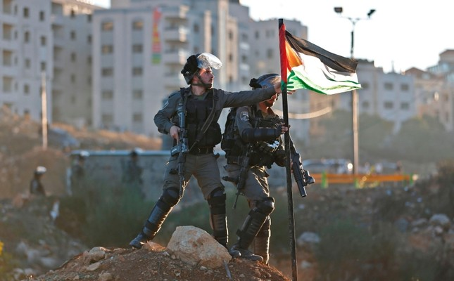 Israeli border guards remove a Palestinian flag as they take position during clashes with Palestinian protesters near an Israeli checkpoint in the West Bank city of Ramallah, Dec. 8, 2017. AFP Photo