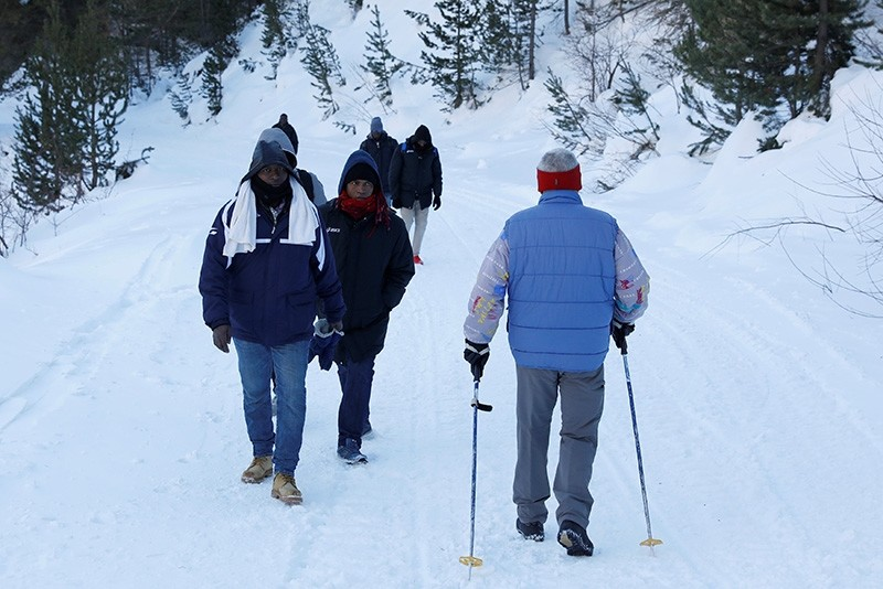 Migrants from Guinea walk along with another group as they pass an Italian man during an attempt to cross part of the Alps mountain range from Italy into France, near the town of Bardonecchia in northern Italy, December 21, 2017. (Reuters Photo)