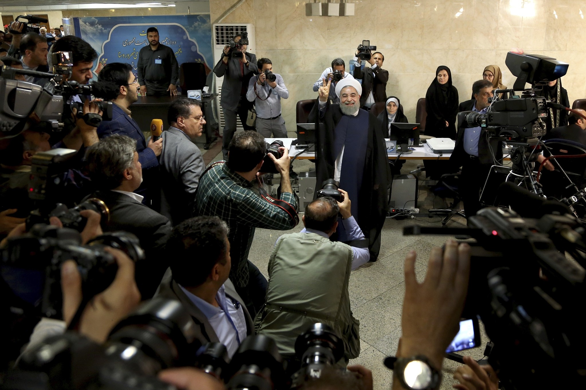 Iranian President Hassan Rouhani waves to media as he attends at the Interior Ministry to register his candidacy for the elections, in Tehran, Iran. (AP Photo)