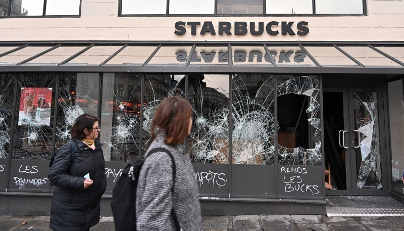 Graffiti is seen on a vandalized Starbucks coffee shop with broken store front windows the day after clashes during a national day of protest by the ,yellow vests, movement in Paris, France, December 9, 2018. (AA Photo)