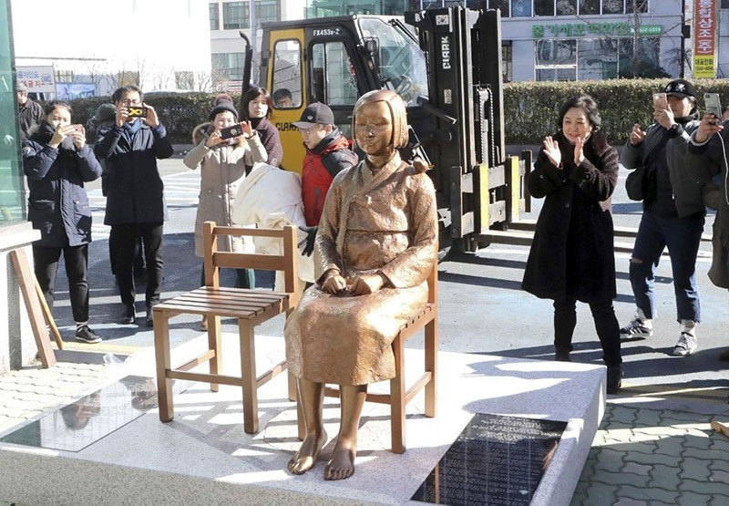 In this Dec. 30, 2016, photo, South Koreans take photos of a comfort-woman statue set up in front of the Japanese consulate in Busan, South Korea. (AP Photo)
