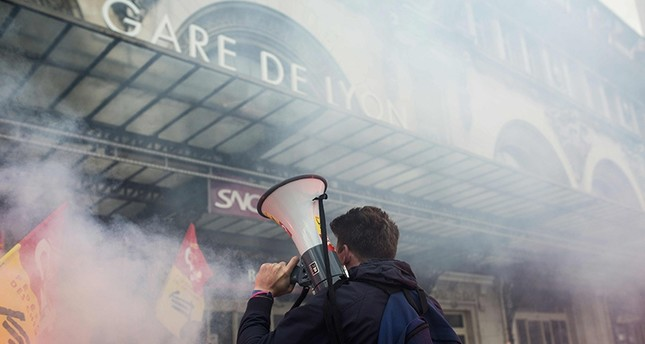 A protester holds a megaphone next to burning flares outside the Gare de Lyon in Paris on April 26, 2016, during a demonstration by railway workers of French state rail operator SNCF, as part of a strike to defend their work conditions. AFP Photo