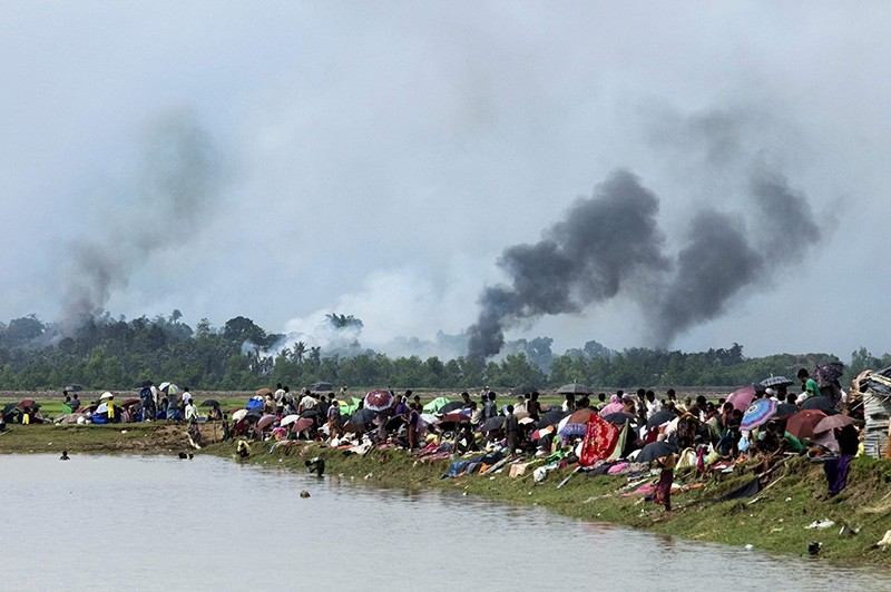Smoke billows above what is believed to be a burning village in Myanmar's Rakhine state as members of the Rohingya Muslim minority take shelter in a no-man's land between Bangladesh and Myanmar (AFP Photo)