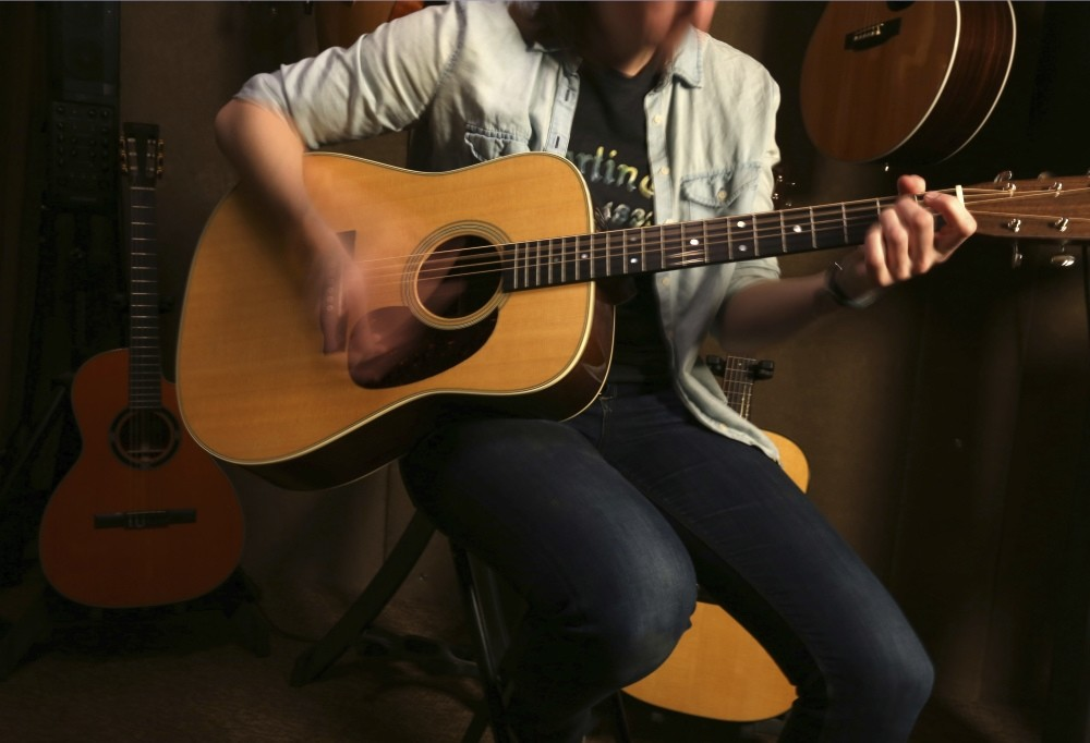 Employee Emily Meixell plays a guitar made with rosewood at C. F. Martin and Co., Pennsylvania.