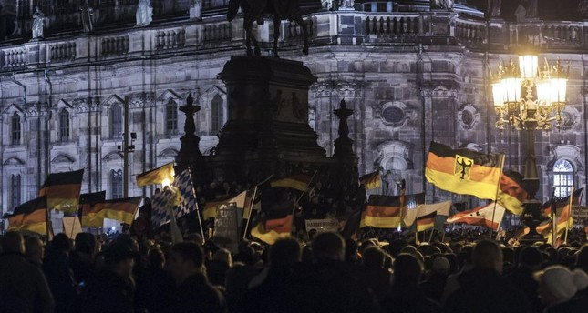 Pegida supporters, a German extremist, racist and Islamophobic group, hold German flags during a demonstration in front of the bronze equestrian statue of King John of Saxony, Dresden, Germany, Dec. 22, 2014.