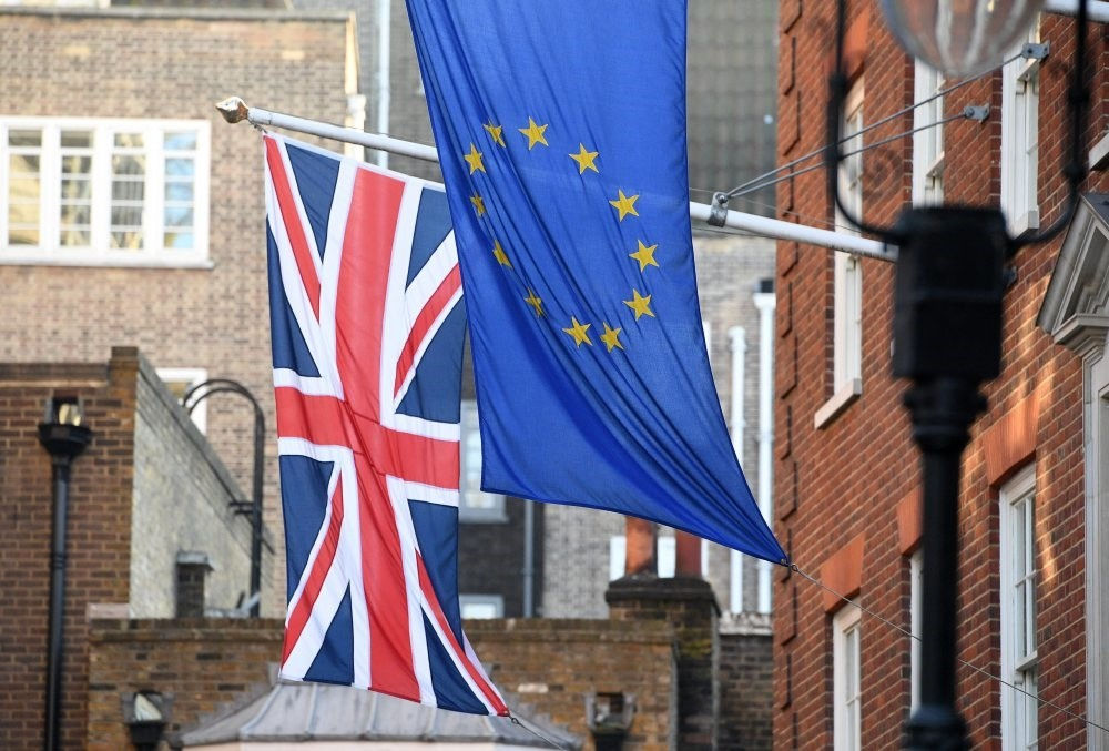 The EU and Union Jack flags fly side by side outside the Europa House in Westminster, London.