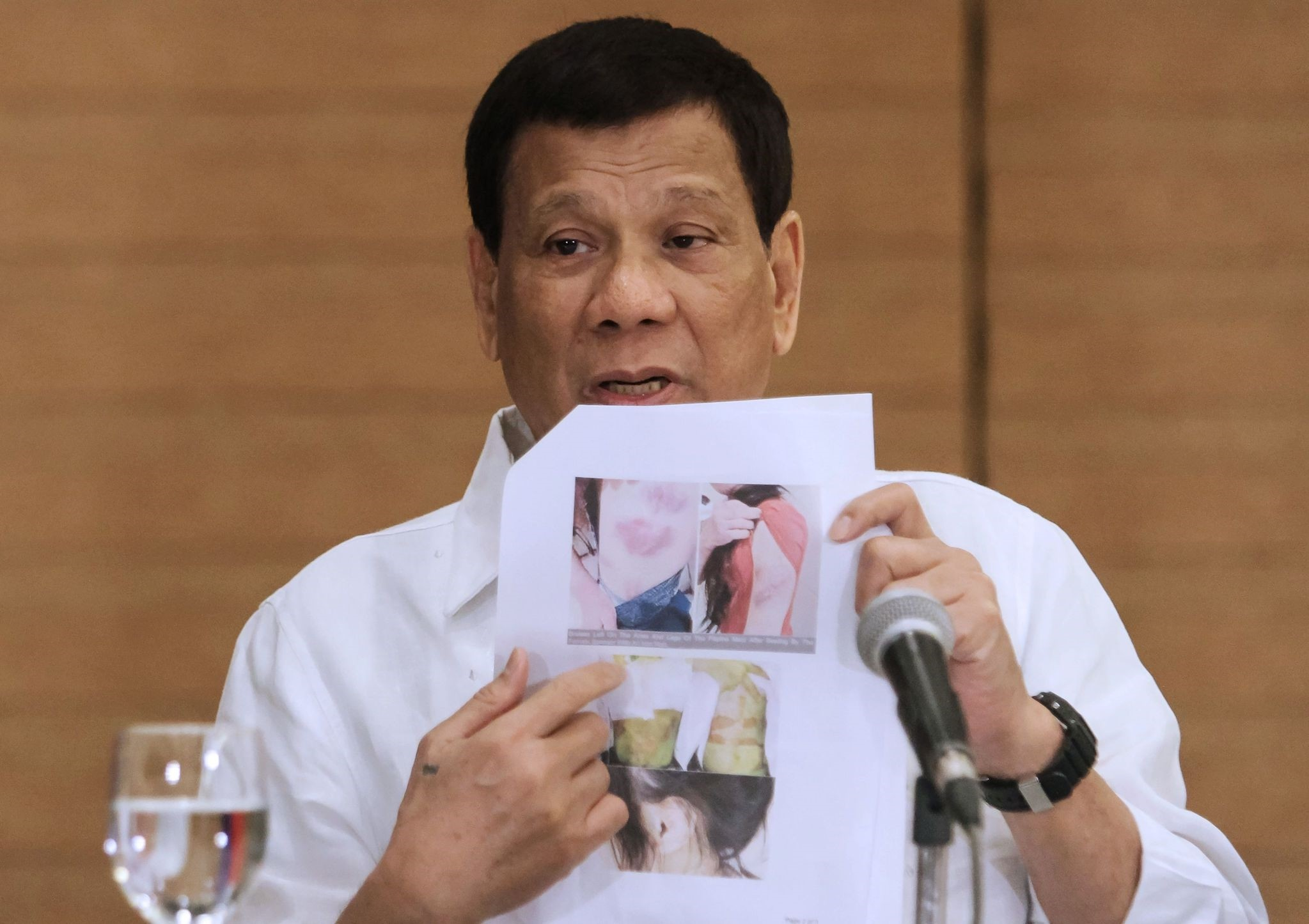Philippine President Rodrigo Duterte shows a photo of a Filipina worker in Kuwait, of whom he said she had been ,roasted like a pig,, during a press conference in Davao City, in the southern island of Mindanao on February 9, 2018. (AFP Photo)