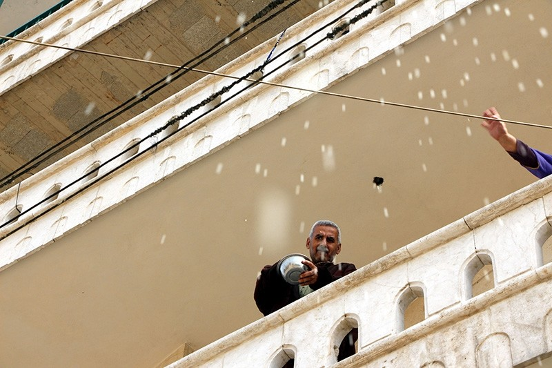 A local resident and his wife throw rice from their balcony to celebrate the liberation of Afrin from PKK/YPG terrorists on March 18, 2018 (DHA Photo)
