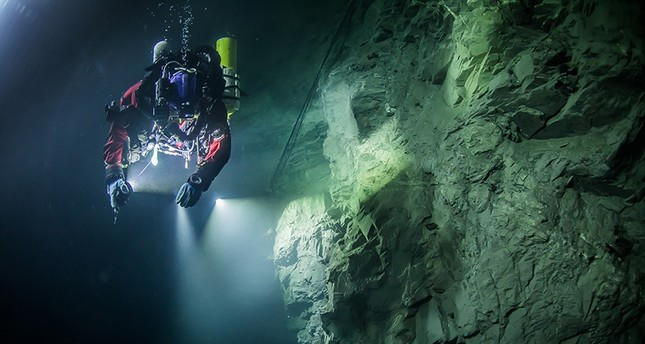 In this underwater photo taken Aug. 21, 2015, in the flooded Hranicka Abyss, Czech Republic, Polish explorer Krzysztof Starnawski is seen examining the limestone crevasse AP Photo