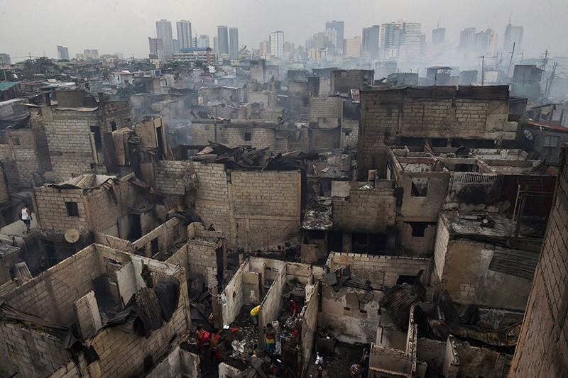 Smoke billows from houses gutted by a fire overnight in an informal settlers area, near the south harbour port, in Manila on February 8, 2017. (AFP Photo)