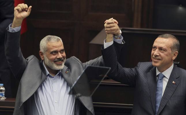 In this file photo, Gaza's Hamas Prime Minister Ismail Haniyeh, left, and then Prime Minister Recep Tayyip Erdoğan, salute together the lawmakers and supporters of Justice and Development Party (AK Party) at the Parliament in Ankara (AP Photo)