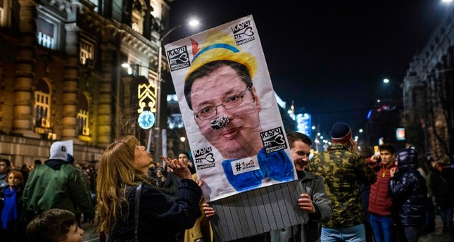 Protesters hold a poster depicting Serbian President Aleksandar Vucic during a demonstration against Serbian President Aleksandar Vucic in Belgrade on February 9, 2019 (AFP Photo)