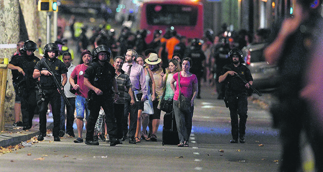 Police accompany people outside a cordoned off area after a van ploughed into a crowd, killing 13 and injuring more than 100 on the Rambla in Barcelona, Aug. 17.