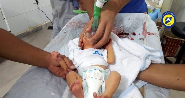 A rescue worker treats an infant who was affected by a chlorine gas attack dropped by regime warplane.