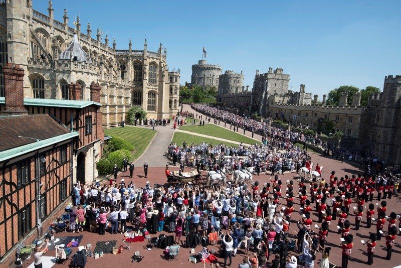 Britain's Prince Harry, Duke of Sussex and his wife Meghan, Duchess of Sussex ride in a horse-drawn Ascot Landau carriage from St George's Chapel towards Windsor Castle during a procession after their royal wedding ceremony in St George's Chapel at Windsor Castle, in Windsor.