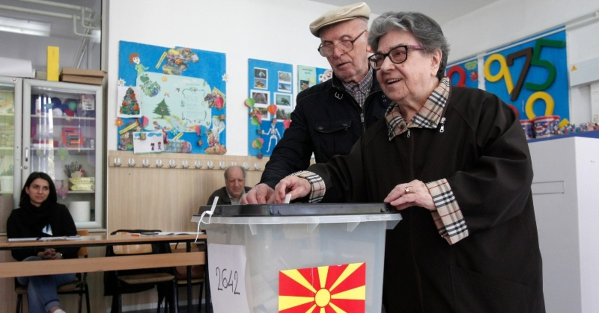 An elderly couple cast their ballots for the presidential elections at a polling station in Skopje, North Macedonia, Sunday, April 21, 2019. (AP Photo)