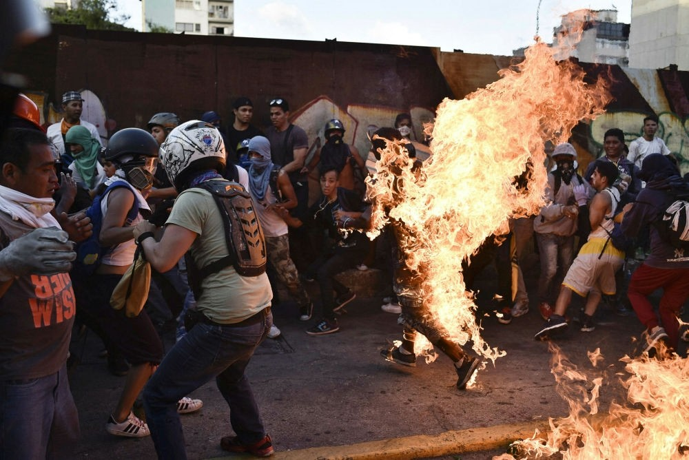 Opposition demonstrators set an alleged thief on fire during a protest against the government of President Nicolas Maduro in Caracas on May 20.
