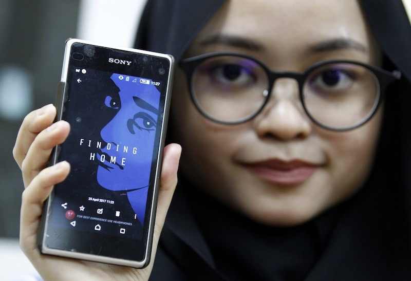 Staff member of the United Nations High Commission for Refugees Izarra Azuddin displays the application ,Finding Home, on her smart phone during a launch at the UNHCR headquarters in Kuala Lumpur, Malaysia. AP Photo
