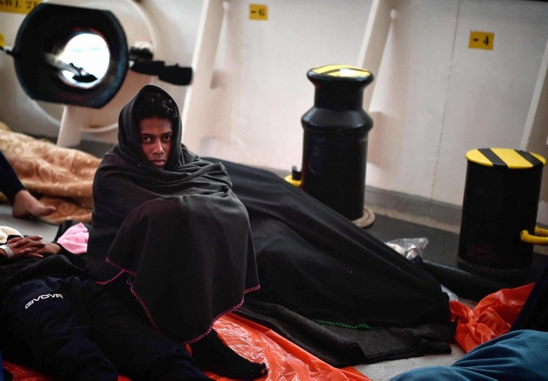 A migrant sits onboard MV Aquarius, a rescue vessel chartered by SOS-Mediterranee and Doctors Without Borders (MSF), some 30 nautical miles off Libya coast (AFP Photo)