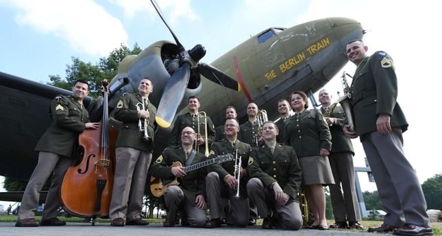 مجموعة من فرقة موسيقية في الجيش الأمريكي أمام إحدى طائرات الحلوى (الفرنسية)