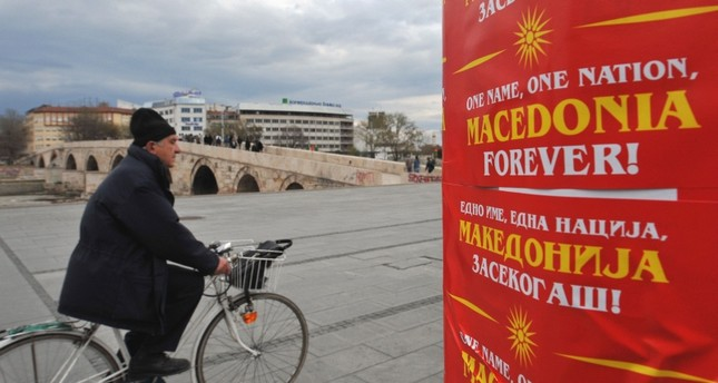 This March 27, 2008 file photo shows a man passing by a panel with placards, saying One name, one nation, Macedonia forever and adorned with the original flag of the Republic of Macedonia in Skopje, Macedonia. (AFP Photo)