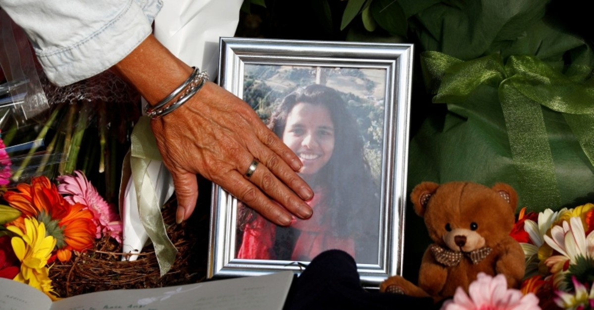 A woman touches a photo at a memorial site for the victims of Friday's shooting, outside Al Noor mosque in Christchurch, New Zealand March 19, 2019. (Reuters Photo