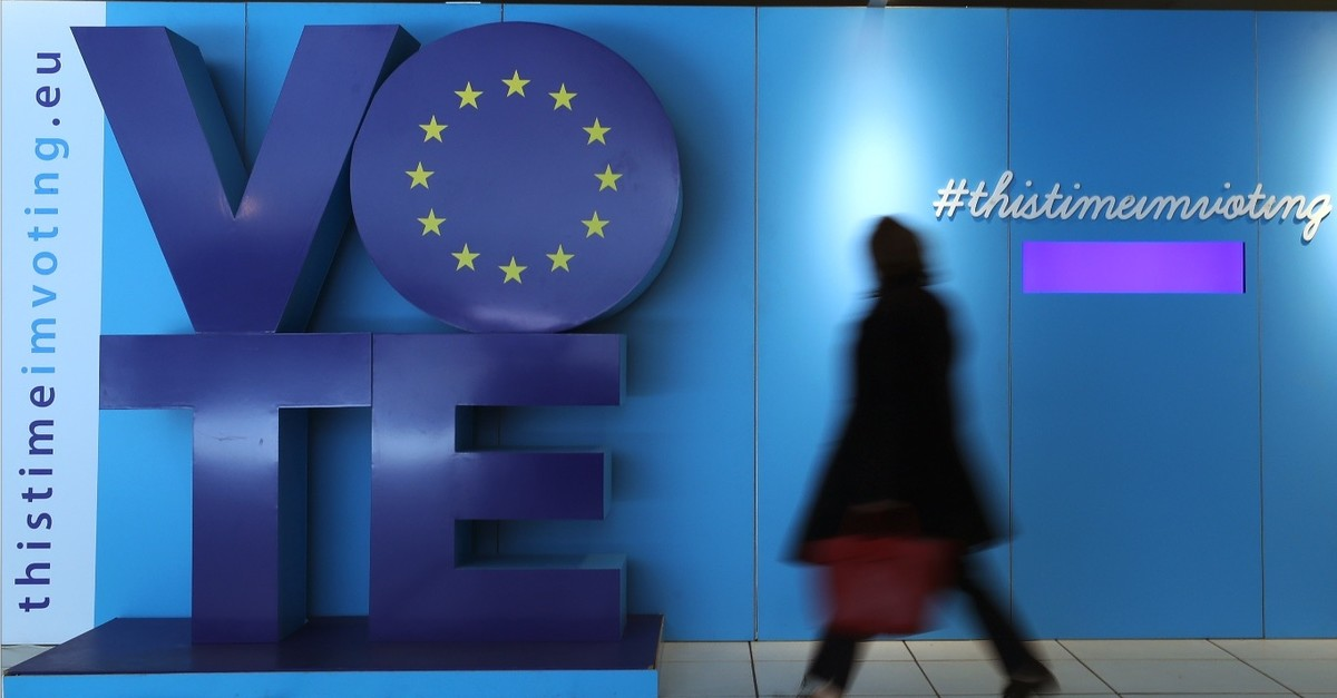A woman walks past an advertising board for the EU elections at the Schuman railway station, Brussels, May 22, 2019.