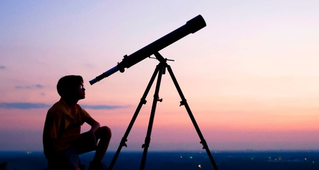 A boy gazes the stars with a telescope.