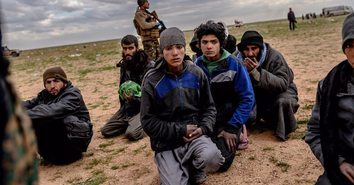 Men and boys suspected of being Daesh members wait to be searched by YPG militants after leaving the Daeshu2019s last holdout of Baghouz, in Syriau2019s northern Deir el-Zour province on Feb. 27, 2019.