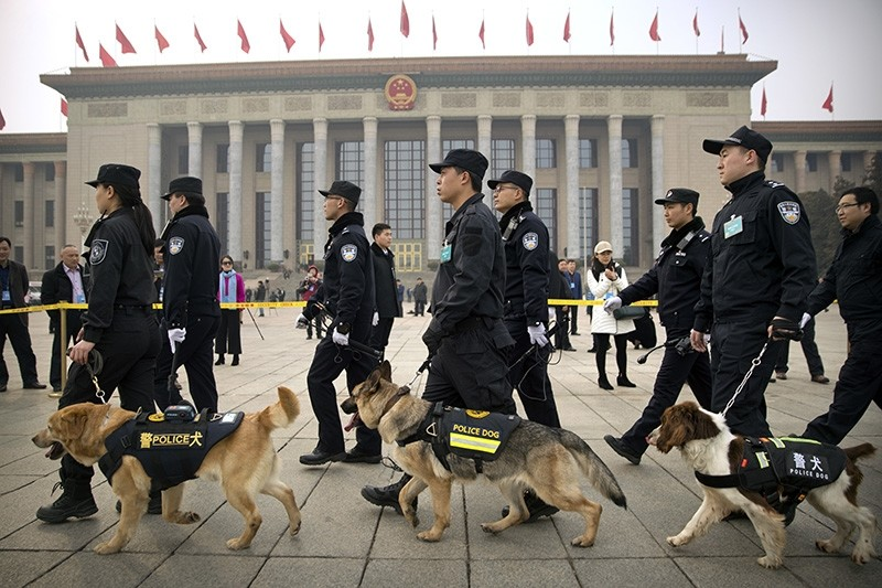 Police dogs and their handlers walk past the Great Hall of the People during the opening session of the Chinese People's Political Consultative Conference (CPPCC) in Beijing, Saturday, March 3, 2018. (AP Photo)