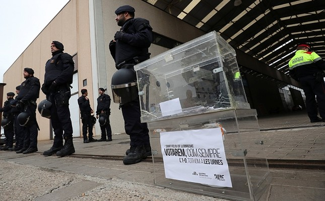 A ballot box, placed by demonstrators, is seen next to Catalan regional police members, who stand guard outside a printing facility, during a raid in search of ballot papers in Sant Feliu de Llobregat, Spain, Sept. 15, 2017. (Reuters Photo)