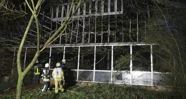 Firefighters stand in front of a burnt out animal house at the Krefeld Zoo in Krefeld, Germany, early Wednesday, Jan. 1, 2020. AP Photo
