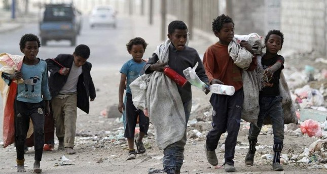 Children walk as they collect empty plastic bottles in a street, Sanaa, Nov. 21, 2019. (REUTERS Photo)