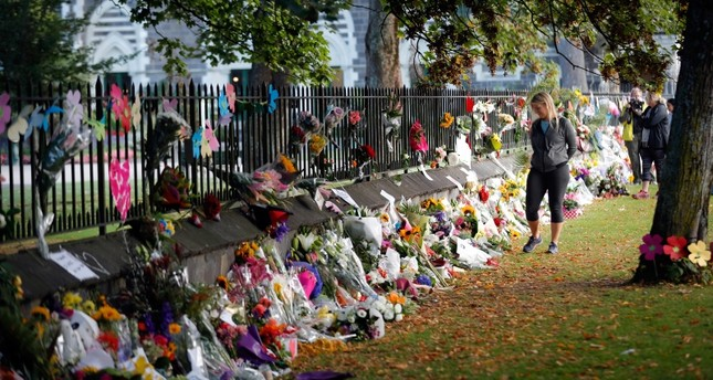 Mourners paying their respects at a makeshift memorial at the Botanical Gardens in Christchurch, New Zealand. (AP Photo)
