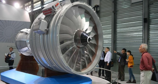 Visitors looking at a full-size model of an aircraft jet engine made by the China Aviation Industry Corporation at the China International Industry Fair in Shanghai.