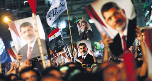 People hold the portrait of ousted Egyptian President Mohammed Morsi during a rally against the military coup that overthrew Morsi and put him into jail, Cairo, Egypt. July 4, 2013.