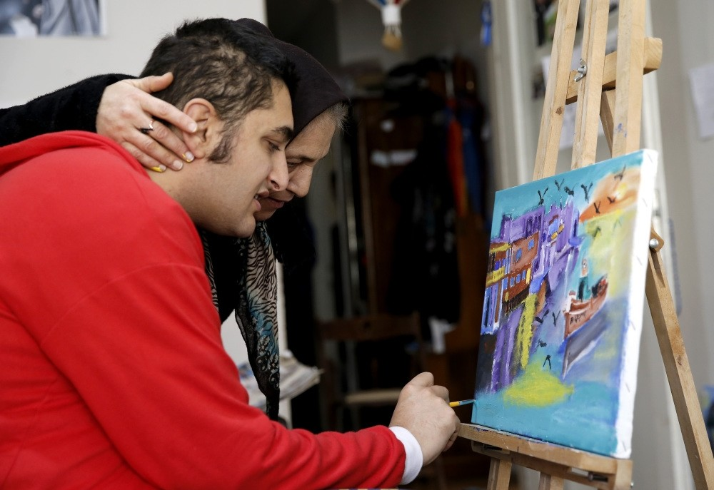 Erkan Ku0131zu0131ldau011f, an autistic artist, draws a painting at home as his mother looks at it. Unofficial numbers show there are more than 1 million people affected by autism in Turkey.