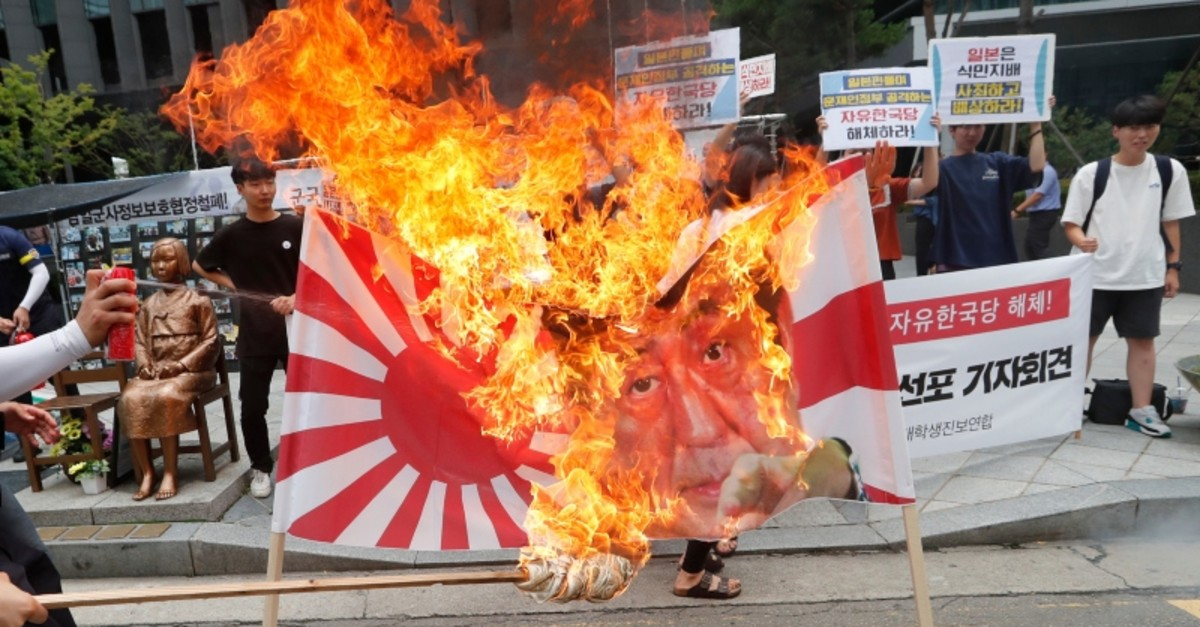 South Korean college students burn a banner showing an image of a Japanese rising sun flag and Japanese PM Shinzo Abe during a rally denouncing the Japanese government, Seoul, South Korea, Monday, July 29, 2019. (AP Photo)