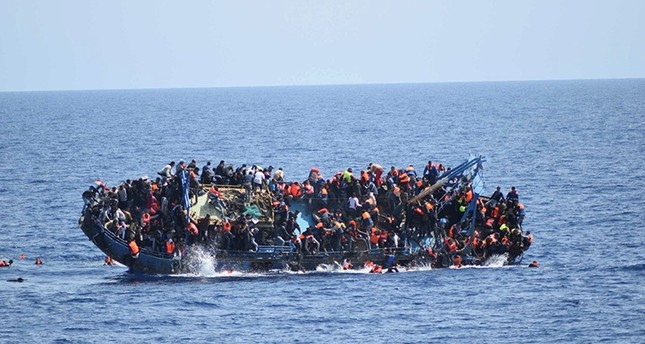 Migrants are seen on a capsizing boat before a rescue operation by Italian navy ships Bettica and Bergamini (unseen) off the coast of Libya in this handout picture released by the Italian Marina Militare on May 25, 2016. (Reuters Photo)