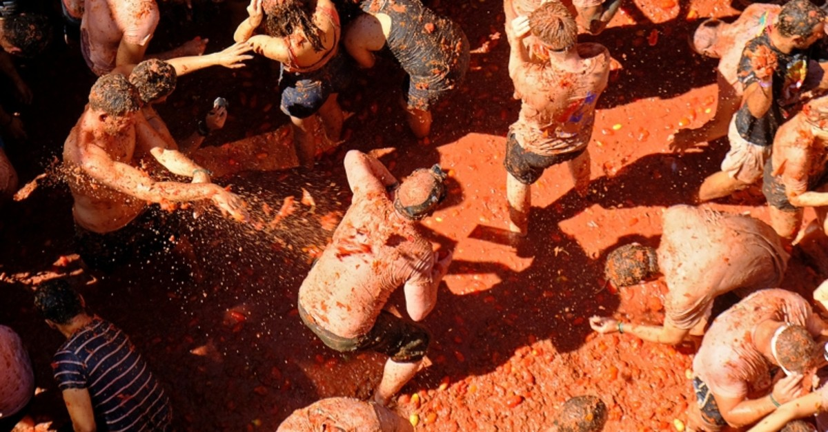 Revellers throw tomatoes at each other, during the annual ,Tomatina,, tomato fight fiesta in the village of Bunol near Valencia, Spain, Wednesday, Aug. 28, 2019. (Reuters Photo)