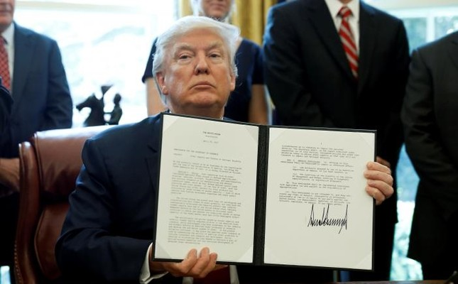 U.S. President Donald Trump holds up a directive ordering an investigation into the impact of foreign steel on the American economy after signing it in the Oval Office of the White House in Washington, U.S., April 20, 2017. (Reuters Photo)