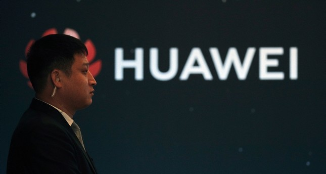 In this Jan. 9, 2019, photo, a security guard stands near the Huawei company logo during a new product launching event in Beijing. (AP Photo)