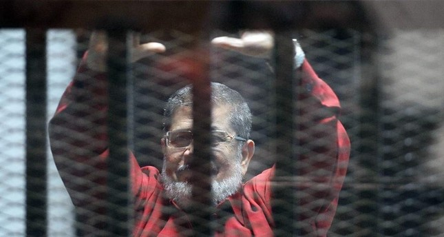 Egypt's first democratically elected President Mohammed Morsi stands behind bars, June 21, 2015. (AFP PHOTO)
