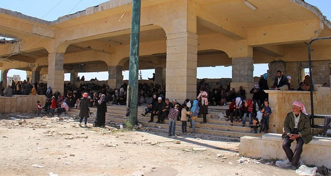 Syrians civilians and pro-regime fighters, from the regime-held towns of Fuaa and Kafraya sit in the shade of a building at the opposition-held transit point of Rashidin, on April 20, 2017, as they wait for the evacuation to resume. (AFP Photo)