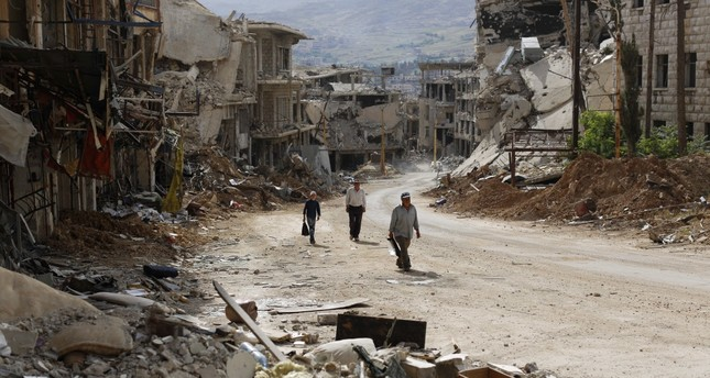 Syrians walk among damaged buildings on a street filled with debri at the mountain resort town of Zabadani in the Damascus countryside, Syria, May 18.