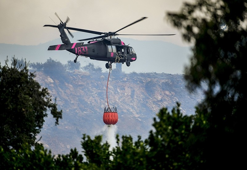 A military helicopter participaties in firefighting efforts in Ventura County against the Thomas Fire in Ojai, California, USA, 07 December 2017. (EPA Photo)
