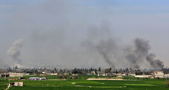 A picture taken on March 7, 2018 shows smoke plumes rising following Assad regime strikes on the village of Mesraba in the besieged eastern Ghouta region on the outskirts of the capital Damascus. (AFP Photo)