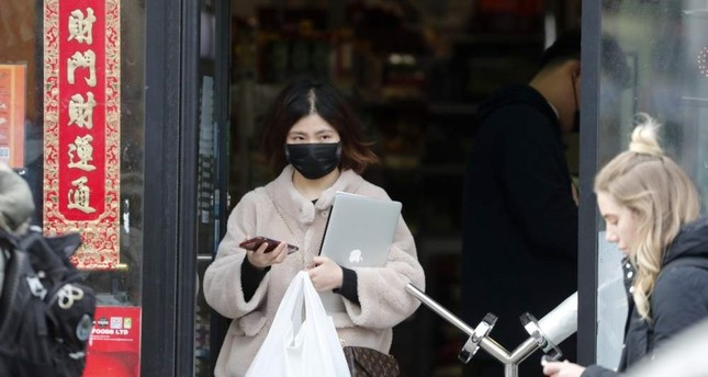 A woman wearing a face mask on her way out of a Chinese supermarket, Brighton, Feb. 11, 2020. AP Photo
