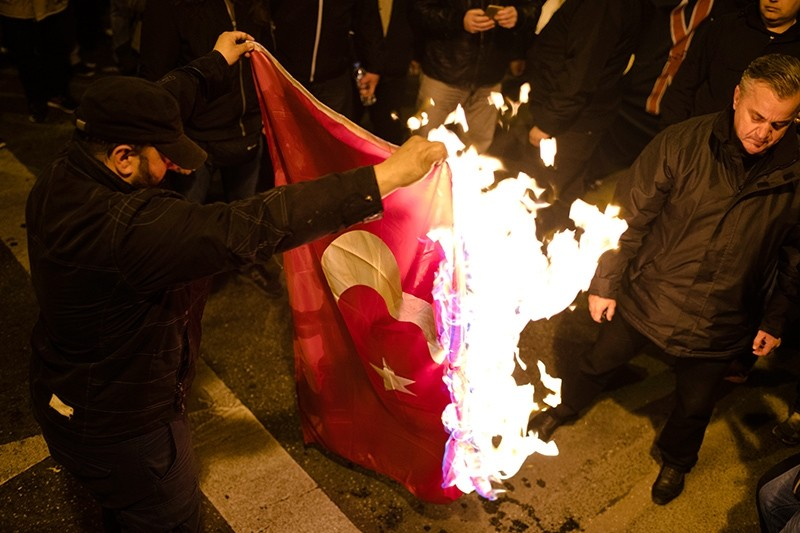Far-right Golden Dawn supporters burn a Turkish flag during a protest in central Athens, Greece, Monday, March 5, 2018. (AP Photo)